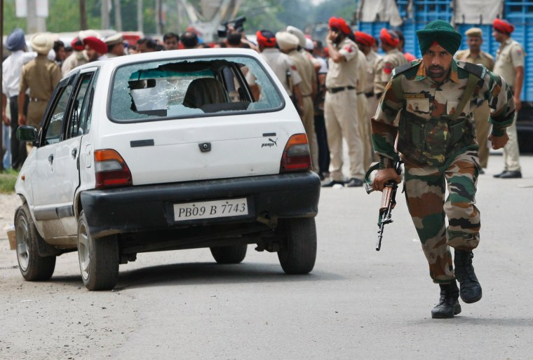 Image: An Indian army soldier runs during a fight in the town of Dinanagar