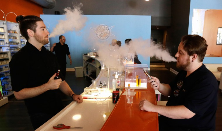 Image: Scot Taylor, left, manager of the Vapor Spot and customer Bruce Schillin, 32 exhale vapor from e-cigarettes