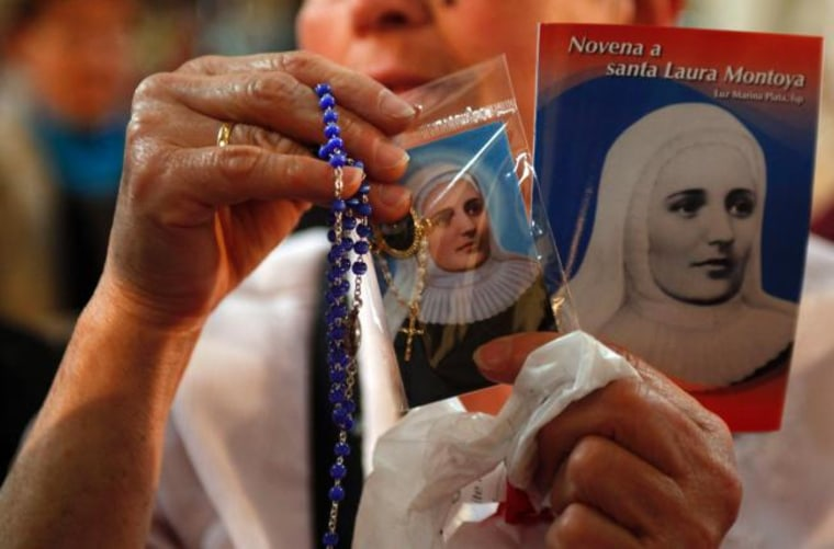 A woman holds up religious articles related to Mother Laura Montoya in the cathedral in Bogota, Colombia.