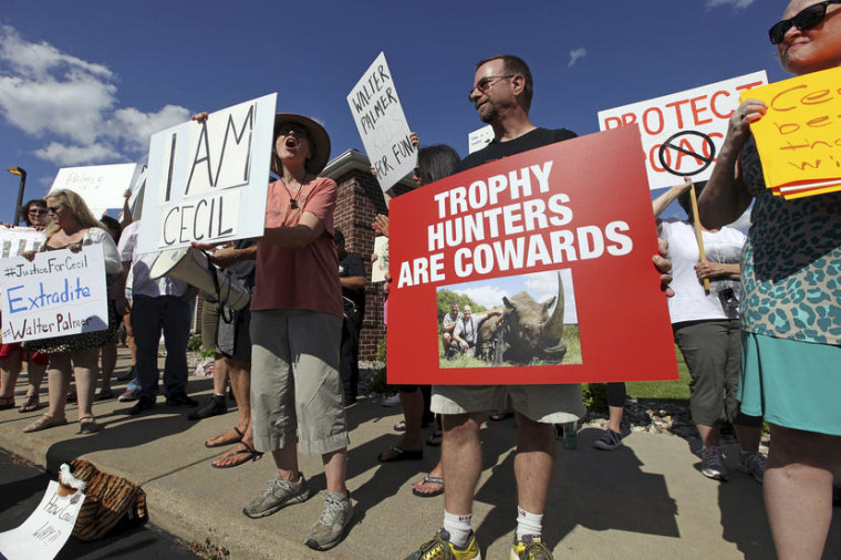 Protesters rally outside the River Bluff Dental clinic against the killing a famous lion in Zimbabwe, in Bloomington, Minnesota July 29, 2015. Wildlife officials on Tuesday accused American hunter Walter Palmer of killing Cecil, one of the oldest and most famous lions in Zimbabwe, without a permit after paying $50,000 to two people who lured the beast to its death. As of Tuesday, Palmer had temporarily closed his office, River Bluff Dental, in Bloomington, Minnesota, amid wishes for his death and widespread criticism of his hunting on social media and under business reviews on Google and Yelp.  REUTERS/Eric Miller - RTX1MC0W