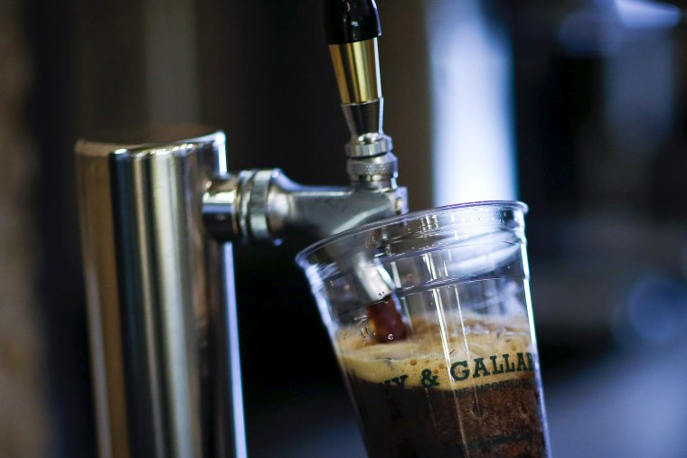 Image: A Guy & Gallard cafeteria employee serves a nitrogen-infused cold brew coffee from Brooklyn-based roaster Gillies Coffee out of a tap at its cafeteria in New York