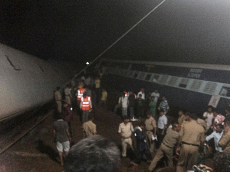 Image: Police and members of the rescue operation stand at the site of a train derailment near Harda, Madhya Pradesh
