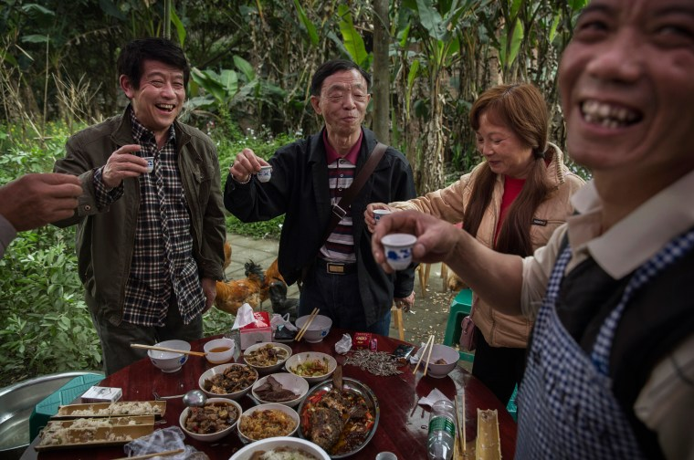 Image:   Local villagers toast a birthday with wine