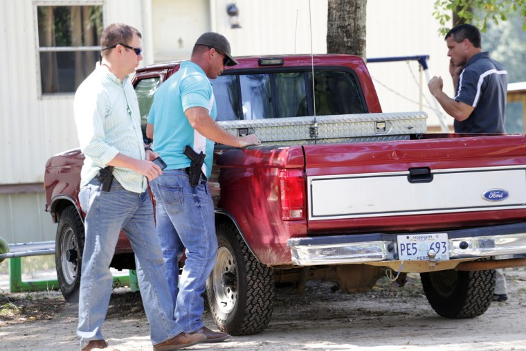 Image: Law officers inspect a vehicle matching the description of the one used in a shooting incident outside Camp Shelby