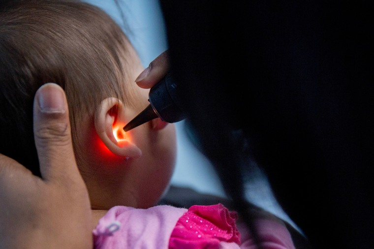 Image: A pediatrician examines an infant's ear in an exam room