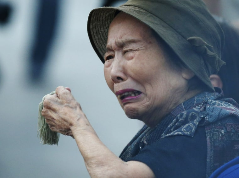Image: Woman reacts as she prays for atomic bomb victims in front of the cenotaph for the victims of the 1945 atomic bombing, at Peace Memorial Park in Hiroshima