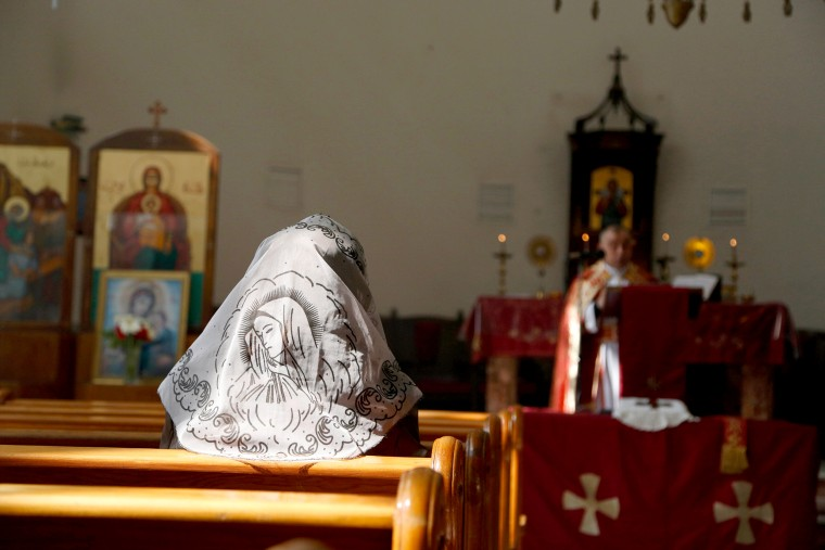 Image: An Assyrian woman attends a mass in solidarity with the Assyrians abducted by Islamic State fighters in Syria
