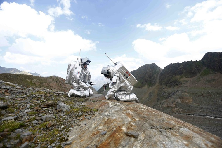 Inigo Munoz Elorza of Spain and Stefan Dobrovolny of Austria (R) take stone samples during a simulated Mars mission on Tyrolean glaciers in Kaunertal, Austria, August 7, 2015.