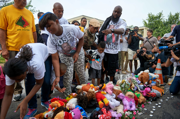 Michael Brown Sr., father of slain 18 year-old Michael Brown Jr. points to stuffed animals along with Brown family members prior to a march of solidarity on August 8 in Ferguson, Missouri.