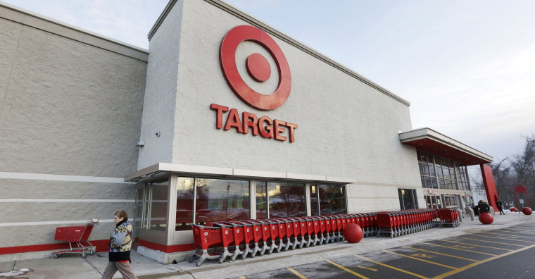FILE - In this Dec. 19, 2013 file photo, a passer-by walks near an entrance to a Target retail store in Watertown, Mass. Target on Friday, Dec. 27, 2013 said that customers' encrypted PIN data was removed during the data breach that occurred earlier this month. But the company says it believes the PIN numbers are still safe because the information was strongly encrypted.