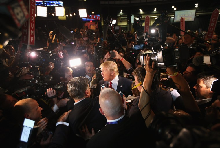 Image: Republican presidential candidate Donald Trump talks to reporters