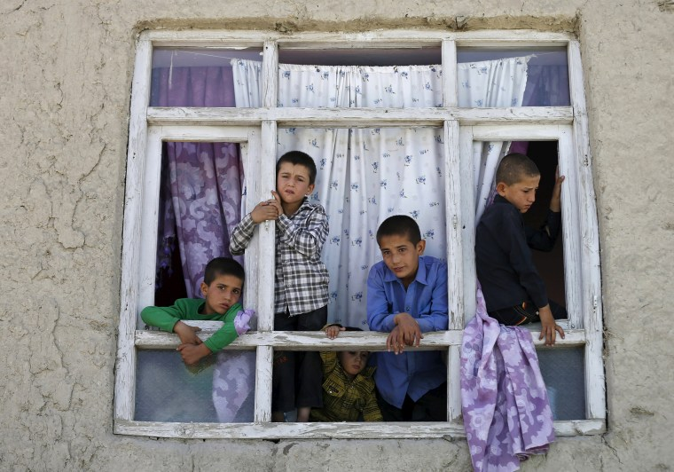 Image: Children look out from the broken window of a house near the site of a car bomb blast at the entrance gate to Kabul airport