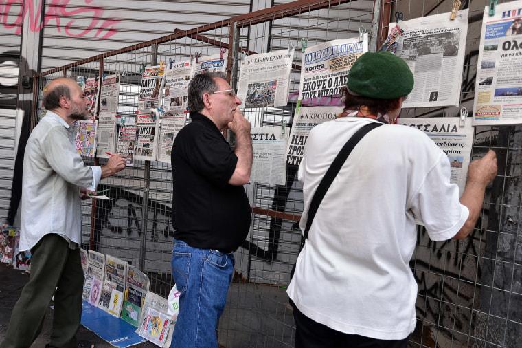 Image: People look at newspaper headlines in Athens