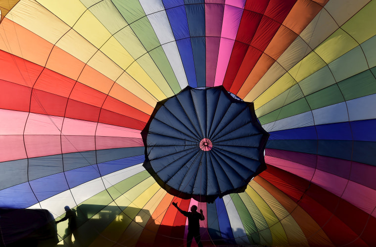 Image: Crew members inflate a balloon during a mass launch at the Bristol International Balloon Fiesta in south west England