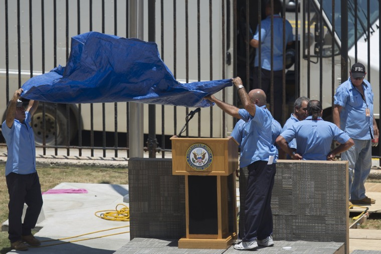 Image: Workers cover the podium with the seal of the U.S. Embassy in Havana where the Embassy opening and flag raising ceremony will take place tomorrow, Havana