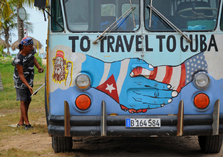 Image: A bus with the Cuban and US flags is seen on a beach in Havana