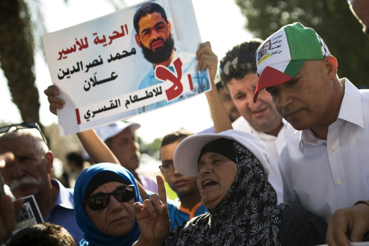 Image: Mother of hunger-striking Palestinian prisoner Mohammed Allan takes part in a protest against force-feeding her son, in Beersheba