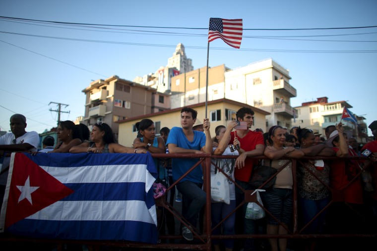 Image: A man holds a U.S. flag while gathering with others on a sidewalk near the U.S. embassy in Havana