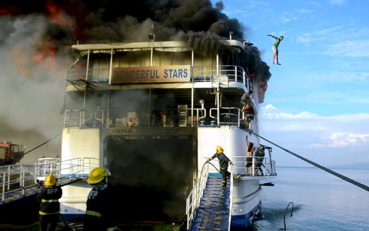 Image: A crew member of MV Wonderful Stars ship jumps off from the burning ship after a fire broke out at the port in Ormoc city, central Philippines