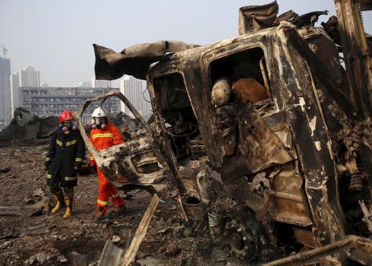 Image: Firefighters walk past a damaged truck at the site of Wednesday night's explosions in Binhai new district of Tianjin