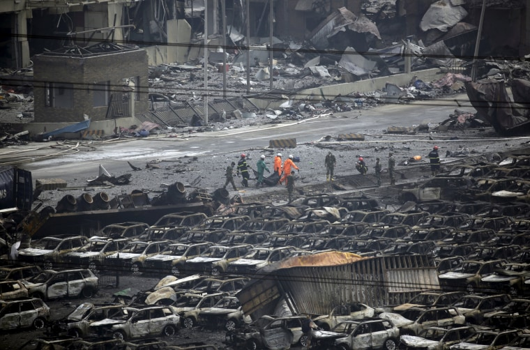 Image: Firefighters walk among debris as they carry out the body of a victim from the site of the explosions towards an ambulance at the Binhai new district, Tianjin