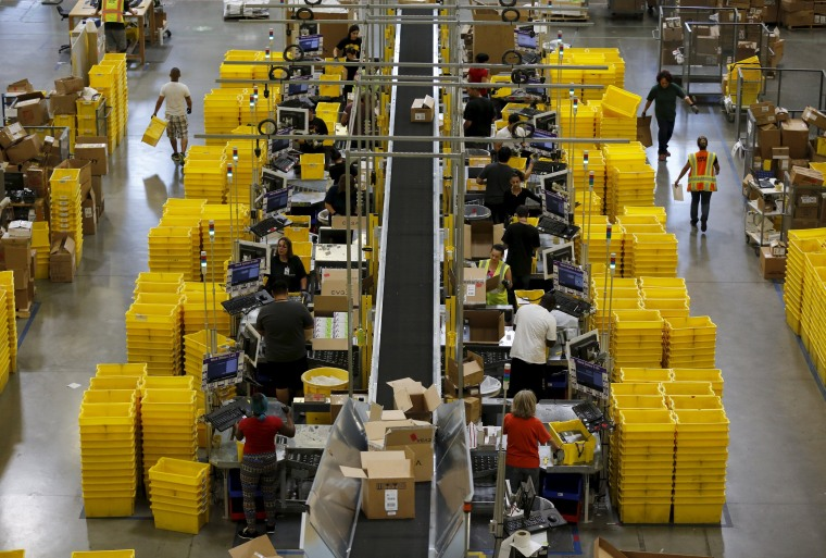 Image: Workers sort arriving products at an Amazon Fulfilment Center in Tracy
