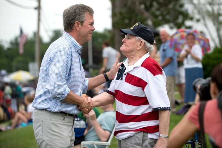 Image: Republican presidential candidate, former Florida Governor Jeb Bush, (L) talks with World War Two veteran Joseph McBreen, 90, along the Independence Day parade route in Merrimack, New Hampshire