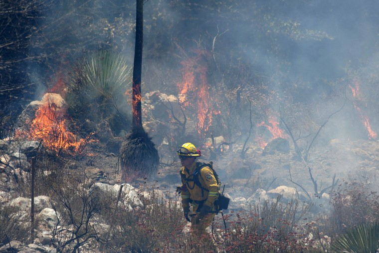 """Image: A firefighter walks past flames during the so-called """"Cabin Fire"""" in the Angeles National Forest near Los Angeles"""