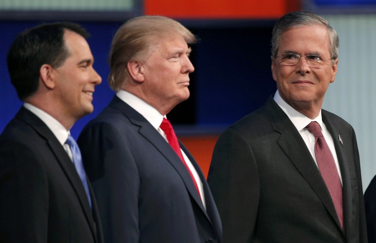 Image: Republican 2016 presidential candidate Bush looks over at Trump and Walker as the candidates pose with seven other candidates at the first official Republican presidential candidates debate of the 2016 U.S. presidential campaign in Cleveland