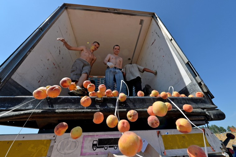 Image: Russian workers throw peaches off a truck