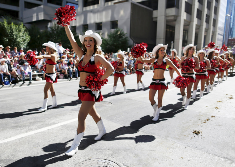 Image: Members of the Calgary Stampeders cheerleading squad march during the Calgary Stampede parade in Calgary