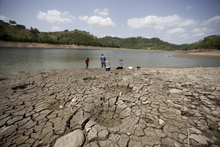 Image: A man and a boy try to fish while standing on the dry shores of the almost empty La Plata reservoir in Toa Alta, Puerto Rico