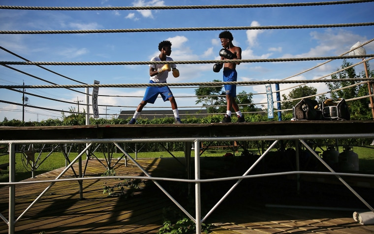 Twin brothers and Hurricane Katrina survivors De'Shane and Dennis Sims, 14, spar at the Running Bear Boxing Club, run by their grandfather Harry Sims next to his home in the Lower Ninth Ward on August 20, 2015 in New Orleans.