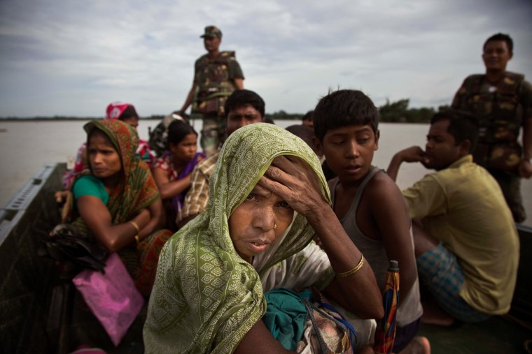 Image: An Indian woman watches from an army boat as she is transported to a safe area