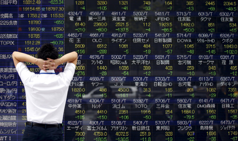 A man looks at a stock quotation board outside a brokerage in Tokyo, August 24, 2015. Asian stocks plunged to 3-year lows on Monday as a rout in Chinese equities gathered pace, hastening an exodus from riskier assets as fears of a China-led global economic slowdown roiled world markets.