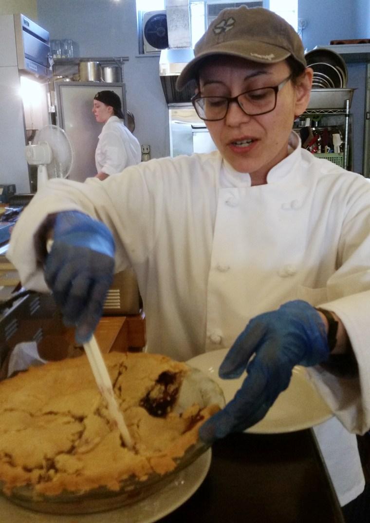 Image: Mundo Vegan co-owner Fanny Fuentes-Phalon cuts a slice of a vegan blueberry apple pie