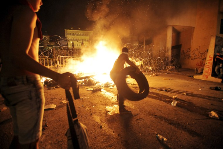 Image: Protesters start a fire during a protest against corruption and against the government's failure to resolve a crisis over rubbish disposal, in front of the government palace in Beirut, Lebanon