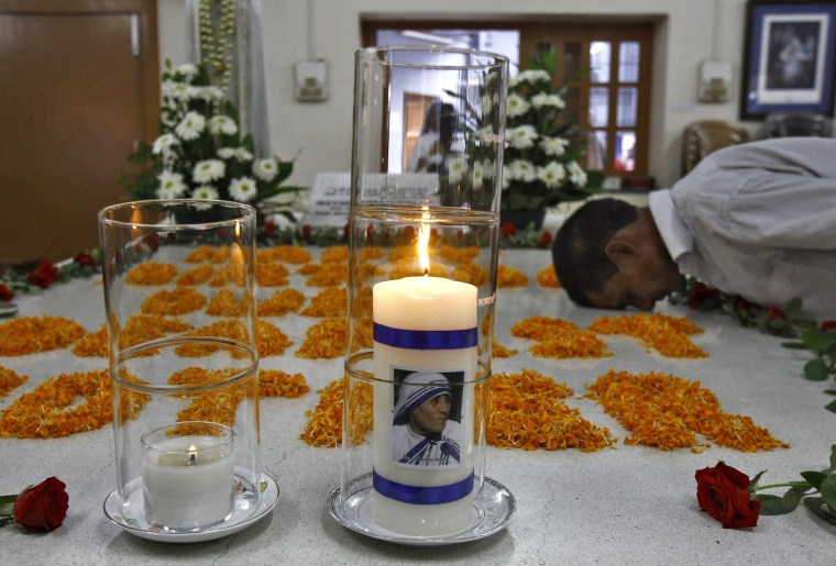 Image: A man prays near image of Mother Teresa on candle, during ceremony to mark her 105th birth anniversary, at her tomb in Kolkata