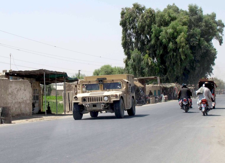Image: Afghan National Police armored vehicle patrols on a street in Lashkar Gah capital of Helmand
