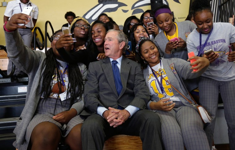 Image: Former President George W. Bush poses for photos with students at Warren Easton Charter High School