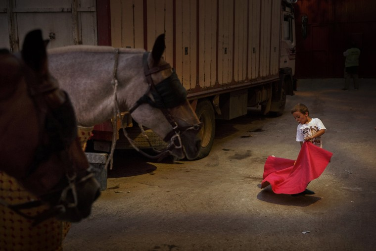 A boy plays the role of a bullfighter in the bullring's backstage in San Sebastian de Los Reyes, Spain on Aug. 28.