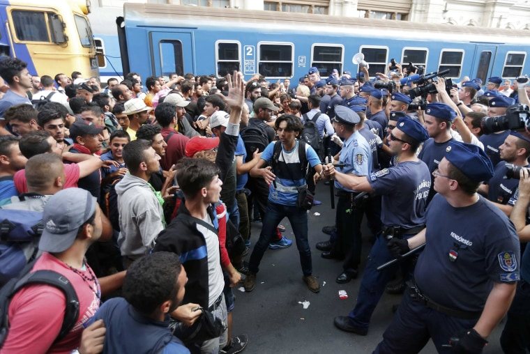 Image: Migrants face Hungarian police in the main Eastern Railway station in Budapest