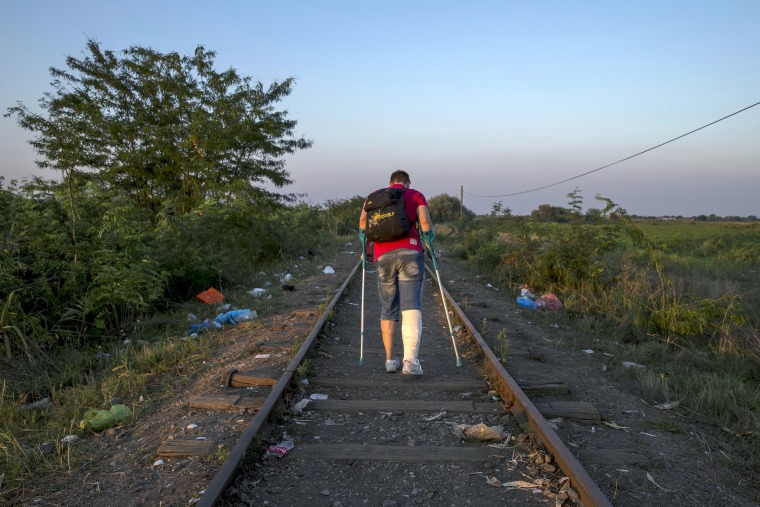 Image: A migrant, hoping to cross into Hungary, walks along a railway track near the village of Horgos in Serbia, towards the border it shares with Hungary