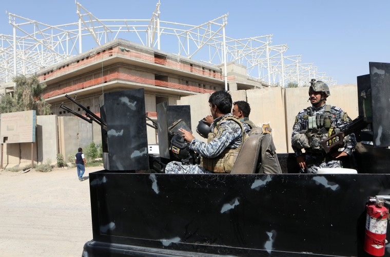 Image: Iraqi security forces guard the entrance to a sports complex