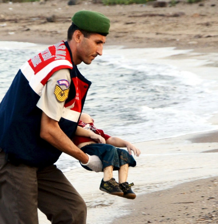 Image: A Turkish official carries a young migrant, who drowned in a failed attempt to sail to the Greek island of Kos