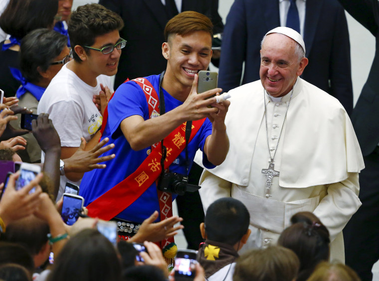 """Image: Pope Francis poses for a selfie during a special audience with members of """"Eucharist Youth Movement"""" in Paul VI hall at the Vatican"""