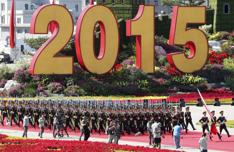 Image: Soldiers of People's Liberation Army (PLA) of China walk past a sign of 2015 as they attend a flag-raising ceremony at the beginning of the military parade marking the 70th anniversary of the end of World War Two, in Beijing