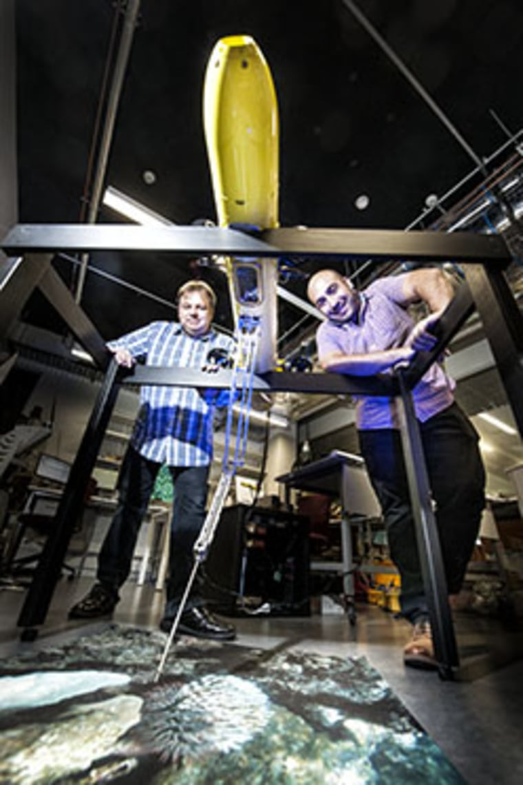 Matt Dunbabin (left) and Feras Dayoub with the COTSbot robot which is designed to search for and kill Crown of Thorns Starfish.