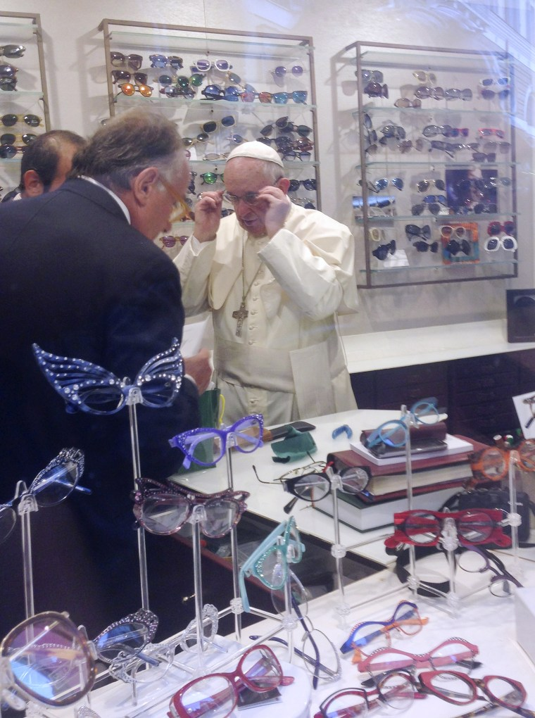 Image: Pope Francis tries on a pair of glasses in an optical store in downtown Rome
