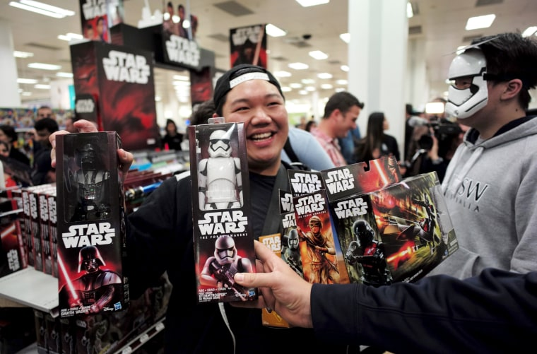 Image: A shopper shows off his haul of new merchandise from the upcoming film 'Star Wars: The Force Awakens
